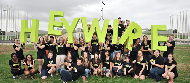 Teens holding HEYWIRE sign in front of Parliament house