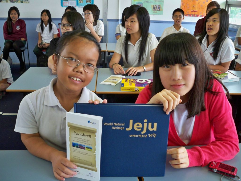 A girl from Cabramatta and girl from Korea reading Jeju, World National Heritage book