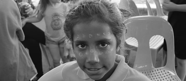 Aboriginal girl with traditionally painted face at Koori Story Exchange program