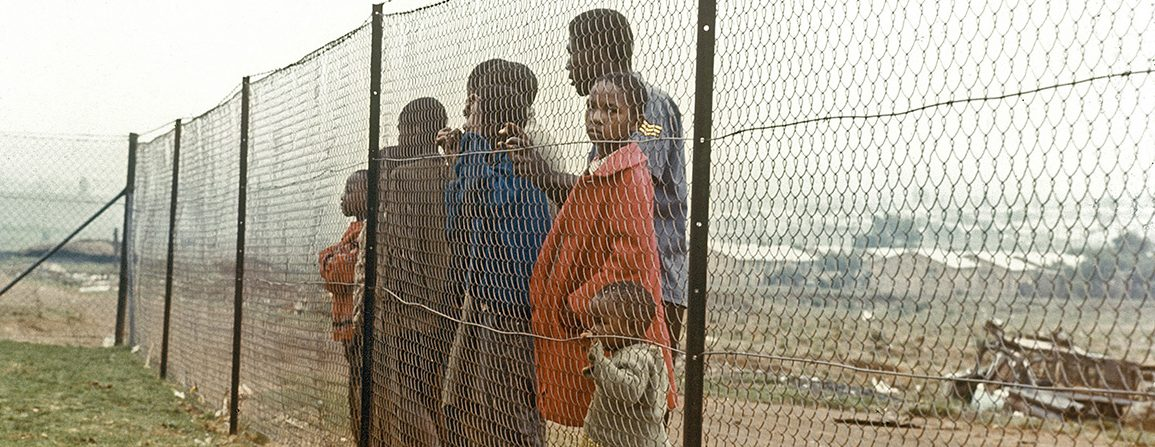 Children behind fence that separates them from the white community near Johannesburg during time of apartheid in South Africa.