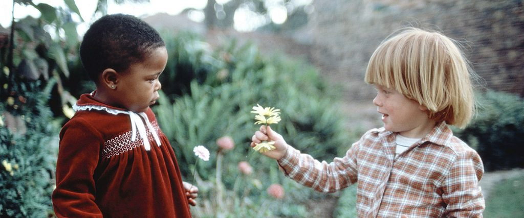 child giving flower to anotherchild